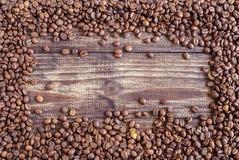 Grains de café dispersés sur un fond en bois 2 photos libres de droits