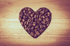 Grains de café en forme de coeur sur le conseil en bois Image stock