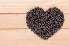 Grains de café en forme de coeur sur un fond en bois Photo libre de droits