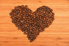 Grains de café en forme de coeur au-dessus du fond en bois en bambou Photos stock