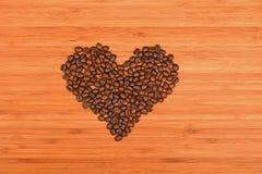 Grains de café en forme de coeur au-dessus du fond en bois en bambou Images stock