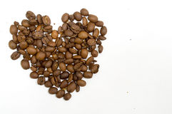 Grains de café en forme de coeur d'isolement sur le blanc Photos stock
