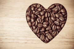 Grains de café en forme de coeur sur le conseil en bois Photos libres de droits