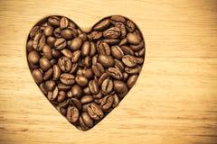 Grains de café en forme de coeur sur le conseil en bois Image libre de droits