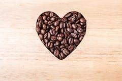 Grains de café en forme de coeur sur le conseil en bois Photos stock