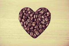 Grains de café en forme de coeur sur le conseil en bois Photo stock
