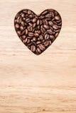 Grains de café en forme de coeur sur le conseil en bois Images libres de droits