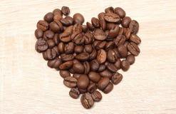 Grains de café en forme de coeur sur le fond en bois Photo libre de droits