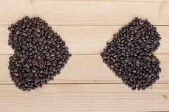 Grains de café en forme de coeur sur un fond en bois Image stock