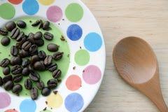 Grains de café en petit cafè de plat et moulu dans la cuillère en bois Photo stock
