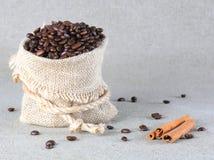 Grains de café en sac et cannelle de toile de jute Image stock