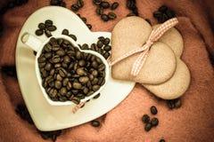 Grains de café en tasse et dessert en forme de coeur Photos libres de droits
