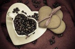 Grains de café en tasse et dessert en forme de coeur sur le brun Photos libres de droits
