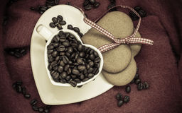 Grains de café en tasse et dessert en forme de coeur sur le brun Images libres de droits