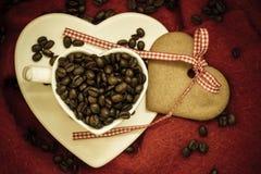 Grains de café en tasse et dessert en forme de coeur sur le rouge Photographie stock libre de droits
