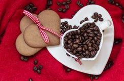 Grains de café en tasse et dessert en forme de coeur sur le rouge Photographie stock