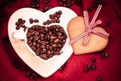 Grains de café en tasse et dessert en forme de coeur sur le rouge Photo libre de droits
