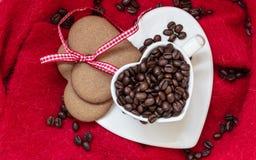 Grains de café en tasse et dessert en forme de coeur sur le rouge Image libre de droits