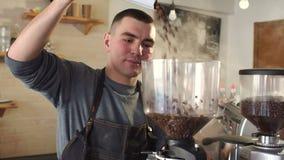 Grains de café endormis en baisse d'homme de barman dans une broyeur de café avant de faire cuire le latte banque de vidéos