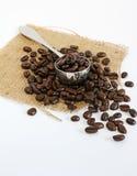 Grains de café et épuisette sur la toile de jute Photos stock