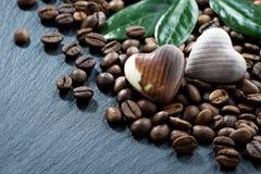 grains de café et bonbons au chocolat sur un fond foncé Images stock