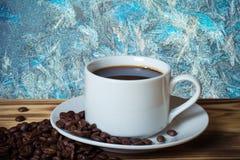 Grains de café et café dans la tasse blanche sur la table en bois vis-à-vis de photo libre de droits