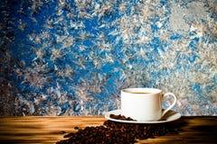Grains de café et café dans la tasse blanche sur la table en bois vis-à-vis de images libres de droits