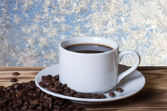 Grains de café et café dans la tasse blanche sur la table en bois vis-à-vis de photos stock
