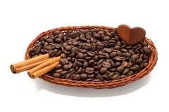 Grains de café et cannelle dans un panier en osier avec le petit coeur doux Photographie stock