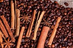 Grains de café et cannelle sur un fond de toile de jute Fin rôtie de fond de grains de café  Pile de grains de café à partir de d Photo libre de droits