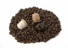 Grains de café et capsule d'isolement sur le fond blanc Photo stock