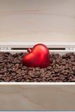 Grains de café et coeur rouge dans une boîte ouverte Photos stock