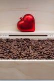 Grains de café et coeur rouge dans une boîte ouverte Image stock
