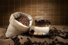 Grains de café et cuvette avec du café Images stock