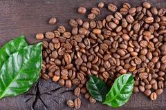 Grains de café et feuilles vertes d'usine de café sur un vieux bureau en bois Vue supérieure des grains de café avec un espace de Image libre de droits