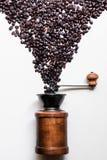Grains de café et rétro broyeur en bois sur le fond blanc Images libres de droits