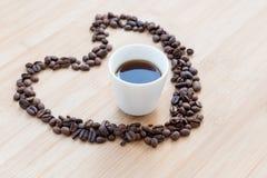 Grains de café et tasse de café noire à l'intérieur d'un coeur Images stock