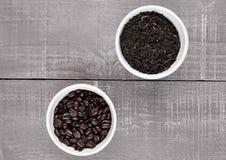 Grains de café et thé lâche dans des cuvettes blanches Images stock