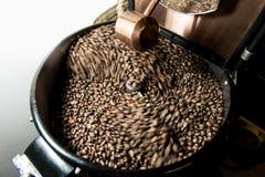 Grains de café fraîchement rôtis dans une machine professionnelle plus fraîche de rotation Photo stock