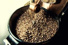 Grains de café fraîchement rôtis dans une machine professionnelle plus fraîche de rotation Images libres de droits