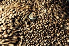 Grains de café fraîchement rôtis dans une machine professionnelle plus fraîche de rotation Photographie stock libre de droits