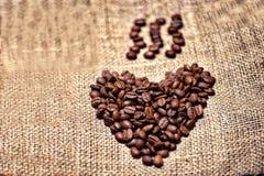 Grains de café frais et aromatiques sur le tissu de vintage image libre de droits