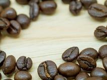 Grains de café frais sur le plancher en bois léger Photographie stock libre de droits