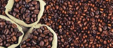 Grains de café frits dans les sacs Panorama photographie stock