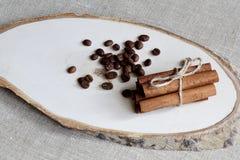 Grains de café parfumés et bâtons de cannelle rôtis attachés avec la corde mince de jute sur le support en bois Fond de fabricati photo libre de droits