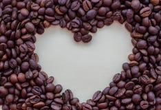 Grains de café rôtis avec l'espace ouvert de coeur au milieu sur le fond blanc Concept de boissons d'arome Photo stock