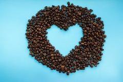 Grains de café rôtis avec l'espace ouvert de coeur au milieu sur le fond bleu Concept de boissons d'arome Image libre de droits
