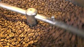 Grains de café rôtis dans la machine de torréfaction clips vidéos