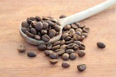 Grains de café rôtis dans une cuillère en bois Images stock