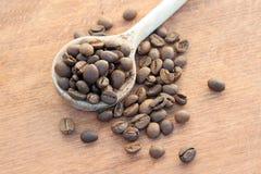 Grains de café rôtis dans une cuillère en bois Photo stock